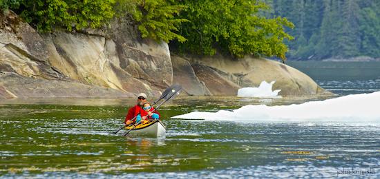 Kayakers enjoy paddling around the icebergs.
